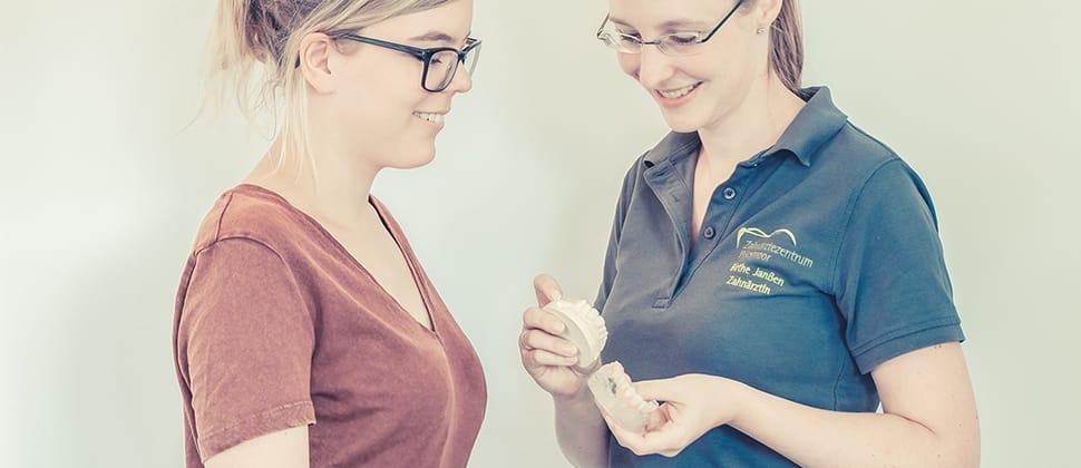 Zahnärztin zeigt Patientin eine Kunststoffschiene für die Zähne